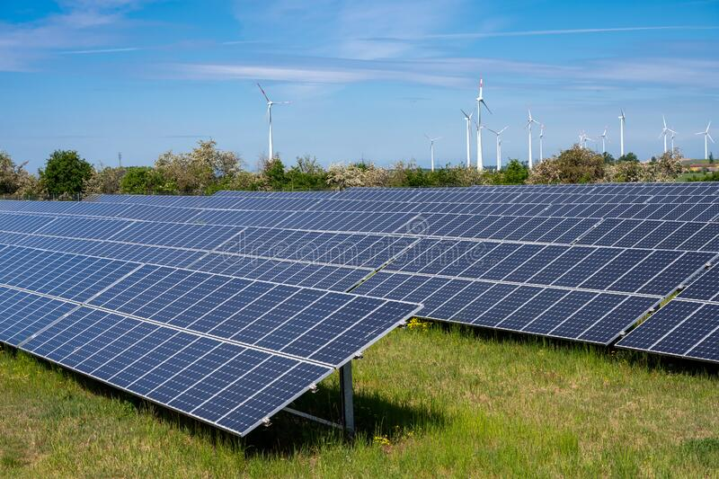Solar panels with wind turbines in the back royalty free stock image