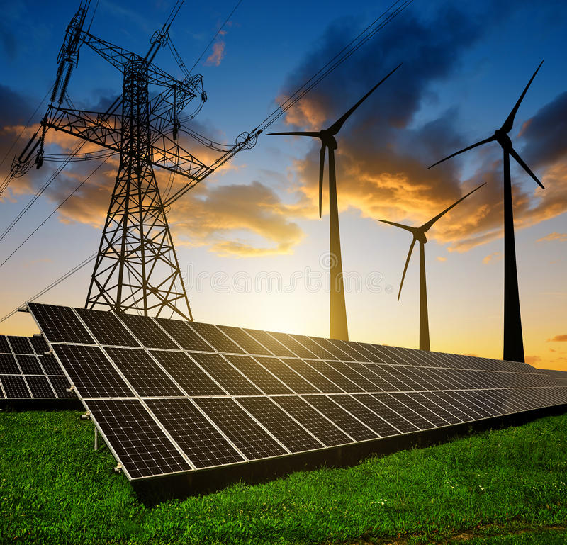 Solar panels with wind turbines and electricity pylon royalty free stock photo