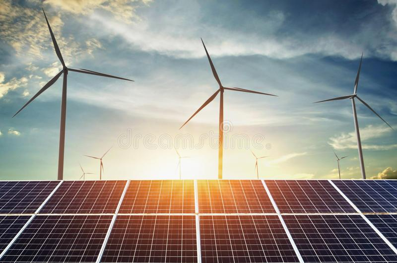 solar panels with wind turbines and sunset. concept clean energy stock image