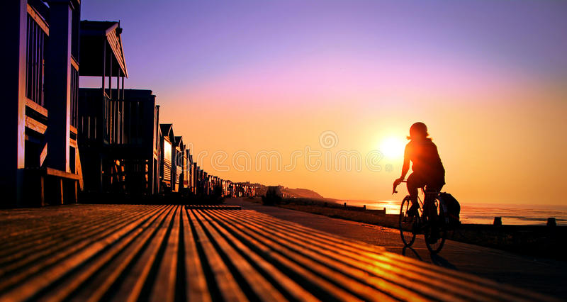 Solar path cyclist. Photo of a lone cyclist enjoying serenity time with nature as the sun sets on the whitstable kent coast reflecting on beach huts along the
