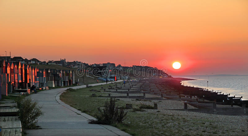 Solar path. Photo of a beautiful kentish sunset going down over the whitstable coast with sun reflecting on beach huts stock images