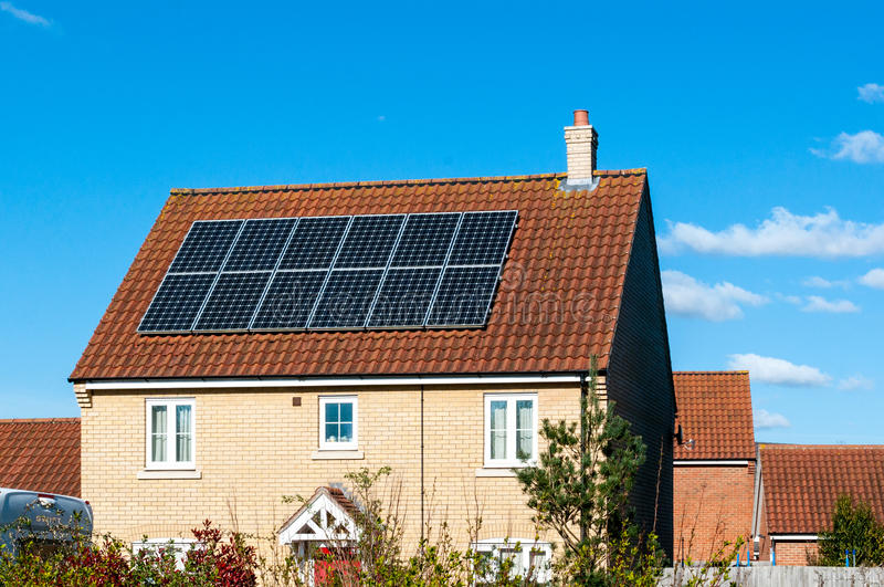 Solar photovoltaic panel array on house roof against a blue sky stock images