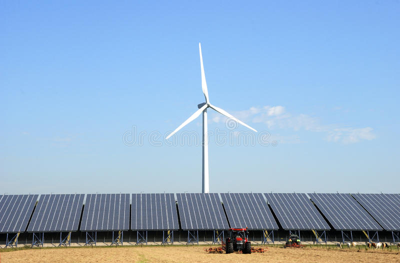 Solar plant with wind turbine at a farm. In the Netherlands.In front two tractors royalty free stock photo
