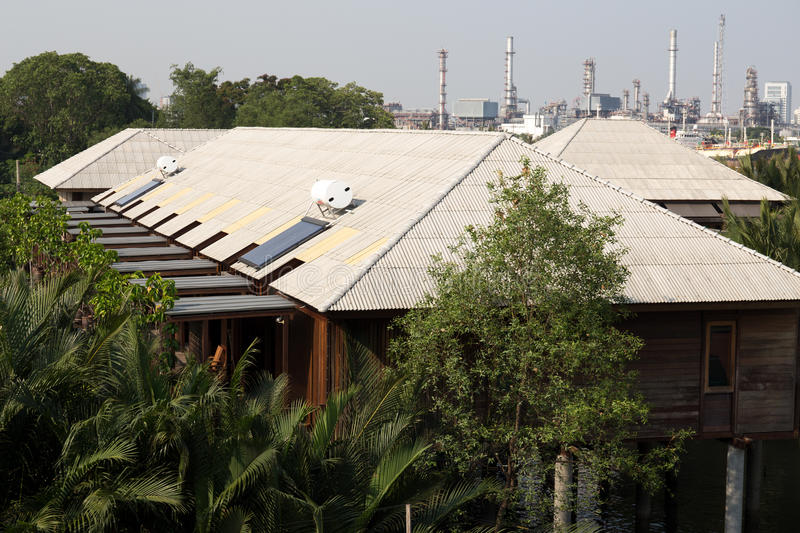 Solar power on the home stay roof with a oil refinery in the background. Solar power on the home stay roof with a oil refinery and tree in the background royalty free stock photography