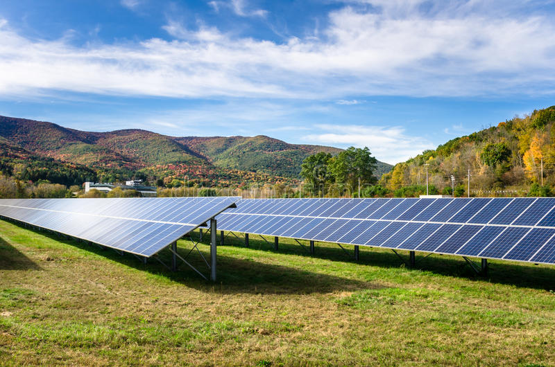Solar Power Plant in a Mountain Landscape. Solar Poser Plant in a Field with Forested Mountains in Background and Blue Sky with Clouds royalty free stock photos