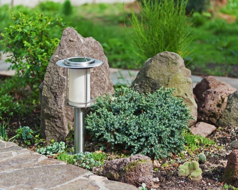 Solar-powered lamp on garden background. royalty free stock photos