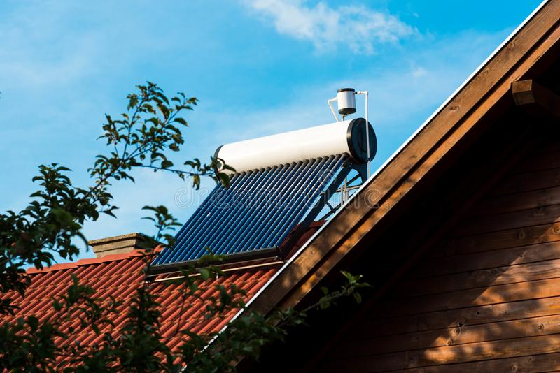 Solar water heater boiler close up shot on residentual house rooftop. Blue sky background royalty free stock images
