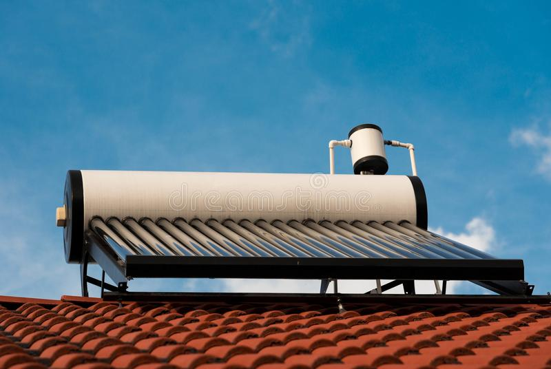 Solar water heater boiler close up shot on residentual house rooftop. Blue sky background stock photo
