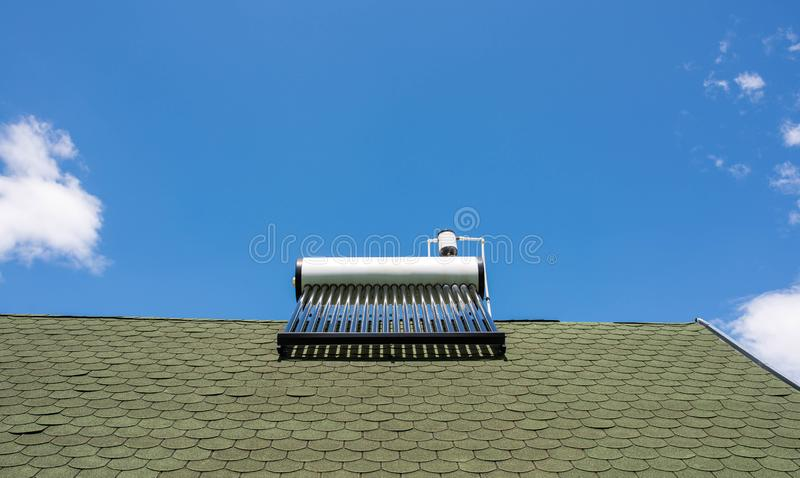 Solar water heater boiler on green rooftop, blue sky with white clouds royalty free stock photo