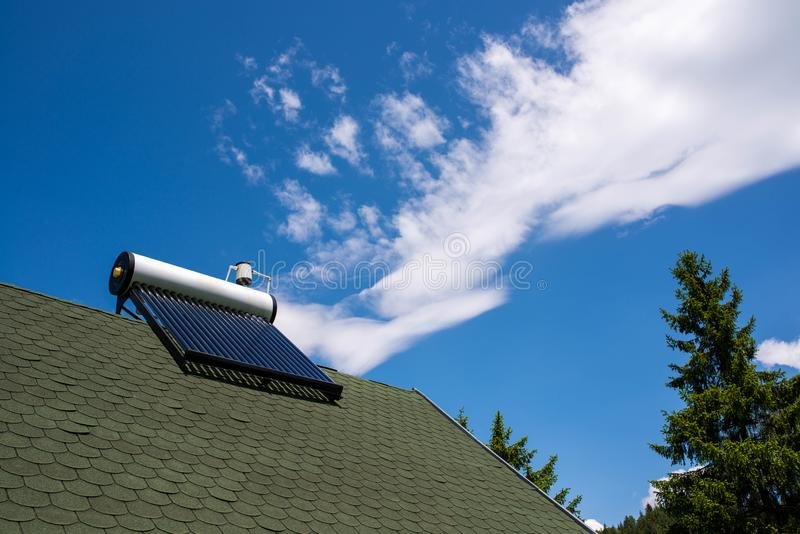 Solar water heater boiler on green rooftop, blue sky with white clouds stock photo