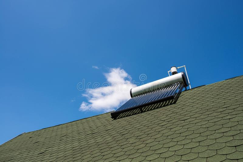 Solar water heater boiler on green rooftop, blue sky with white clouds. Background royalty free stock photography