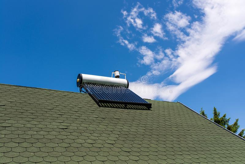 Solar water heater boiler on green rooftop, blue sky with white clouds. Background, pine trees royalty free stock photos
