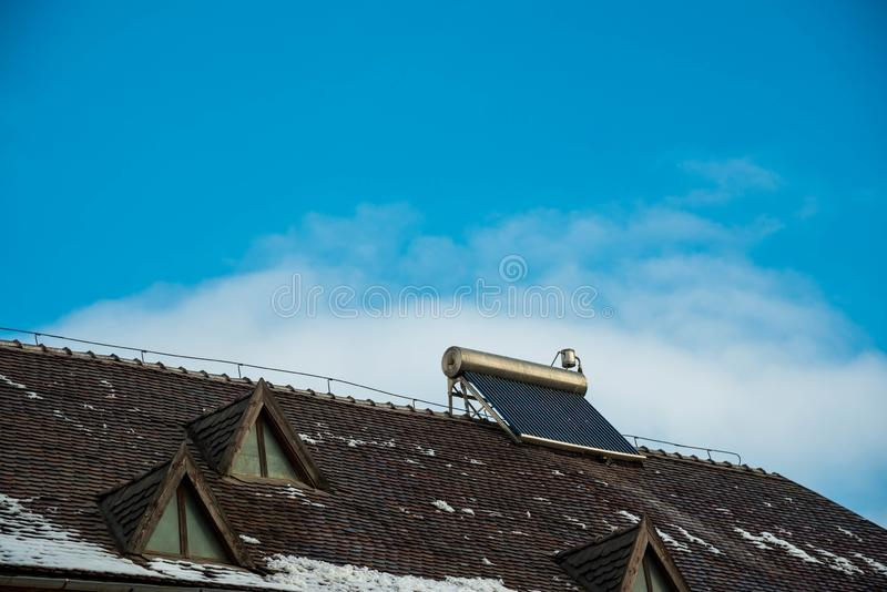 Solar water heater boiler on old buildings rooftop. Blue sky with white clouds background royalty free stock photography
