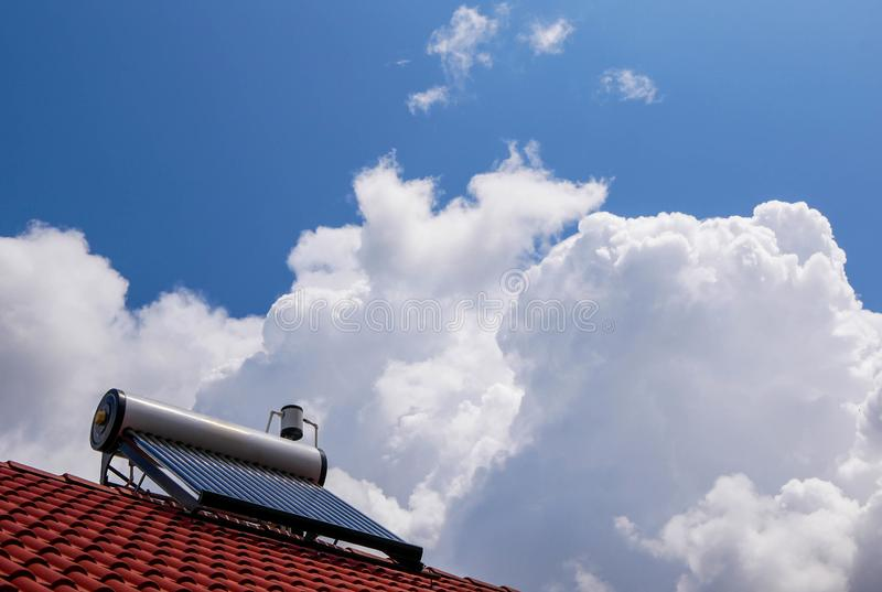 Solar water heater boiler on red rooftop, beautiful blue sky with white clouds. Space for text royalty free stock photo