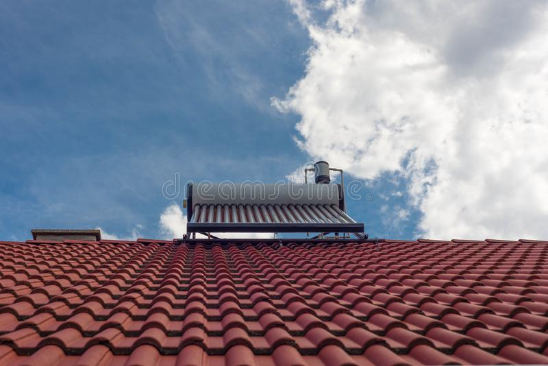 Solar water heater boiler on residentual house rooftop. Blue sky with white sky background stock photos
