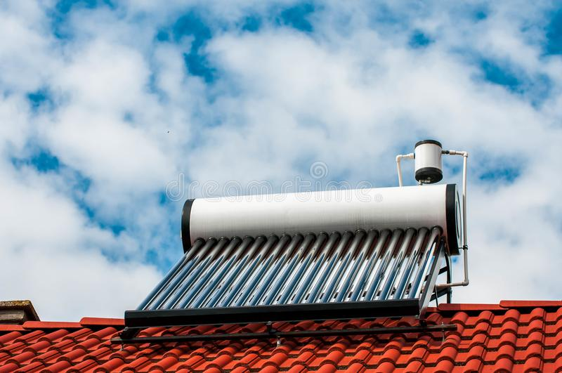 Solar water heater boiler on residentual house rooftop. Blue sky with white sky background royalty free stock image