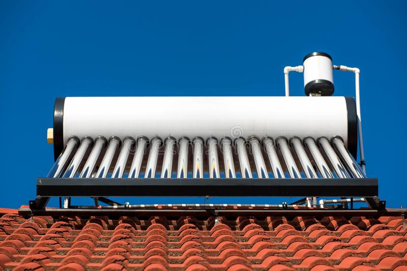 Solar water heater boiler on residentual house rooftop. Perfect blue sky background stock images