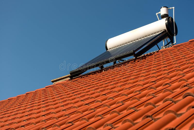 Solar water heater boiler on residentual house rooftop. Perfect blue sky background stock photo