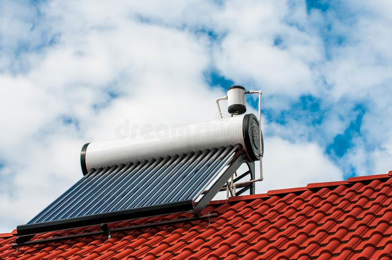 Solar water heater boiler on residentual house rooftop. Blue sky with white sky background stock photo