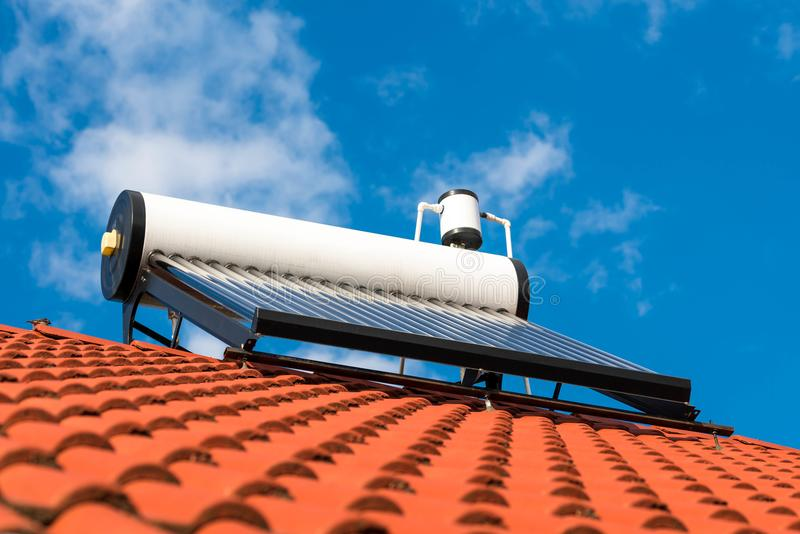 Solar water heater with boiler on roof top. Blue sky with white clouds background royalty free stock image