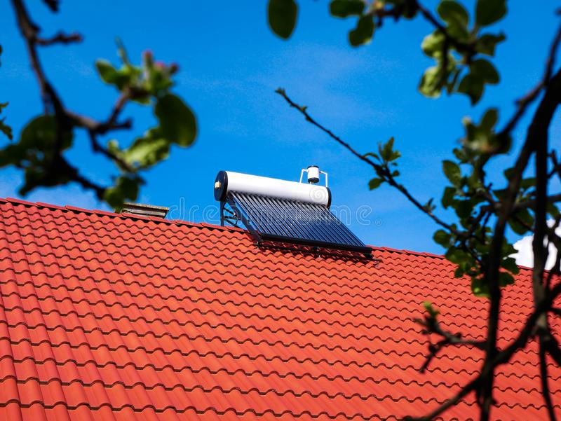 Solar water heater boiler on rooftop, beautiful blue sky with white clouds. In the background, copy space stock images