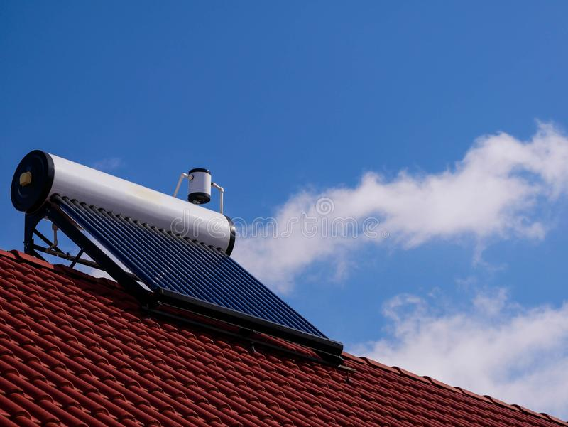 Solar water heater boiler on rooftop, blue sky with white clouds. On the background stock image