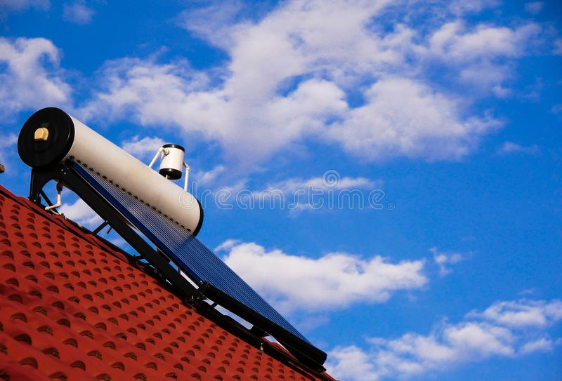 Solar water heater boiler on rooftop, blue sky with white clouds in the background,. Copy space royalty free stock image