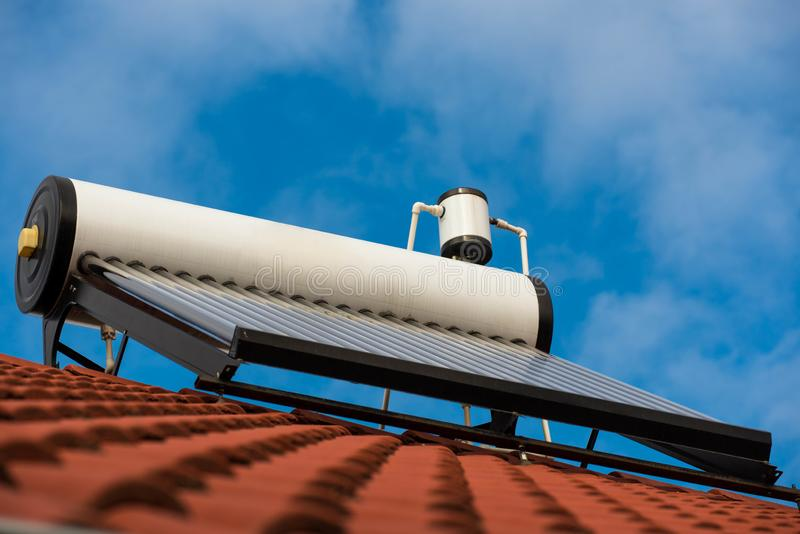 Solar water heater boiler on rooftop, blue sky with white clouds. In the background stock photos