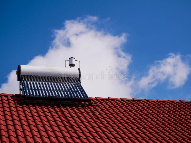 Solar water heater boiler on rooftop, blue sky with white clouds. On the background royalty free stock photos