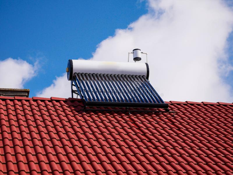 Solar water heater boiler on rooftop, blue sky with white clouds. On the background stock photography