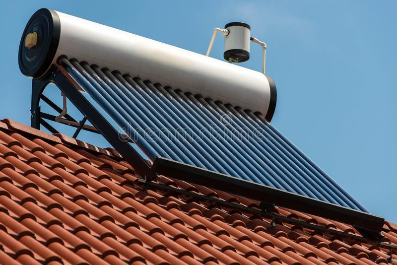 Solar water heater boiler on rooftop close up shot. Blue sky background royalty free stock images