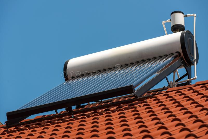 Solar water heater boiler on rooftop close up shot. Blue sky background stock images