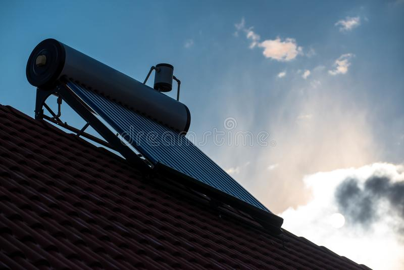 Solar water heater boiler on rooftop at early morning. Visible sun in white clouds royalty free stock photo