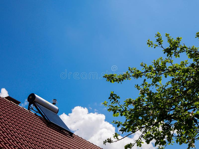 Solar water heater boiler on rooftop, green apple tree. Blue sky white clouds, conceptual green house image royalty free stock images