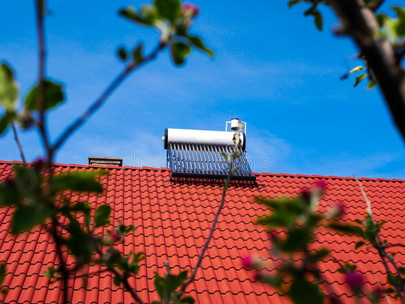 Solar water heater boiler on rooftop, green defocused leaves. Conceptual green house image royalty free stock photo