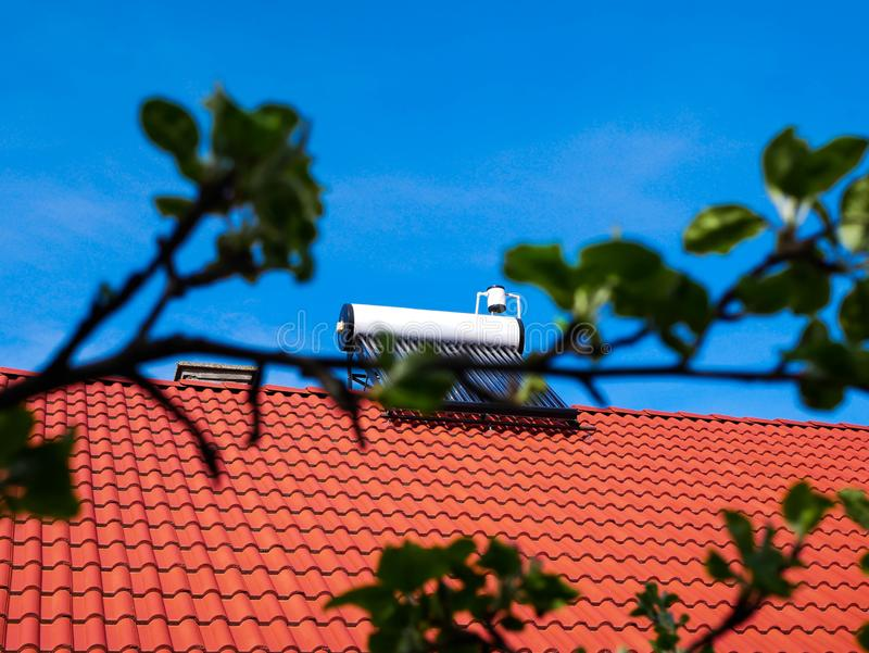 Solar water heater boiler on rooftop, green defocused leaves. Conceptual green house image stock image