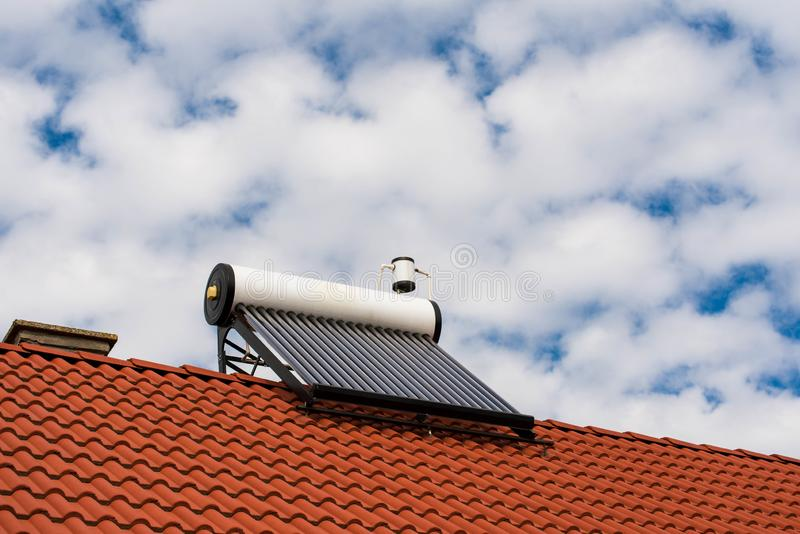 Solar water heater boiler on rooftop. Blue sky with white clouds background stock image