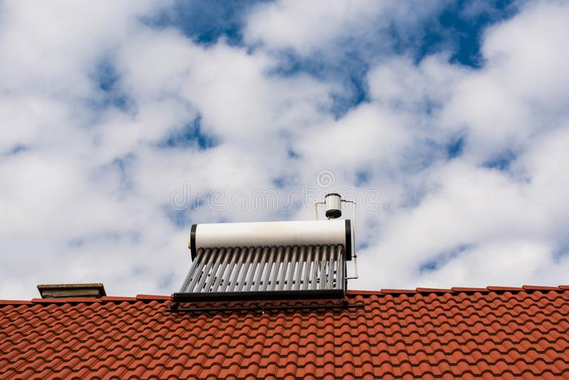 Solar water heater boiler on rooftop. Blue sky with white clouds background stock photography