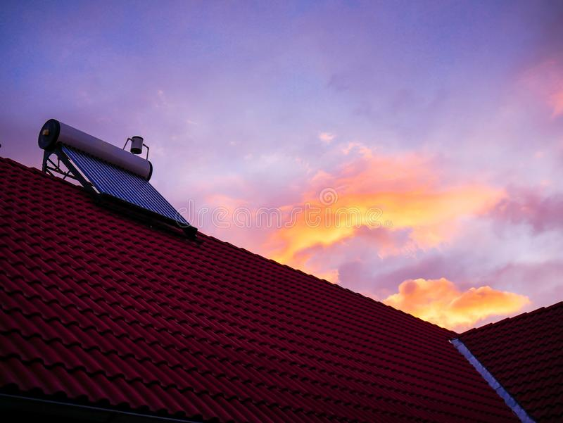Solar water heater boiler on rooftop, sunrise, cold morning, orange clouds on blue sky. Background stock image