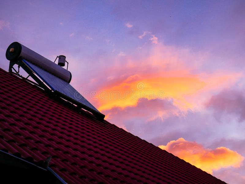 Solar water heater boiler on rooftop, sunrise, cold morning, orange clouds on blue sky. Background royalty free stock image