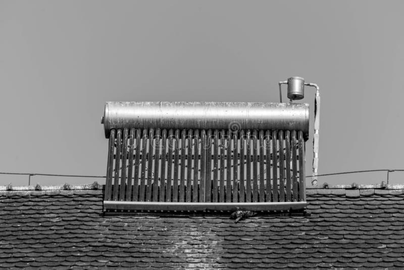 Solar water heater boiler on rooftop, visible bird excrements. On the boiler stock image