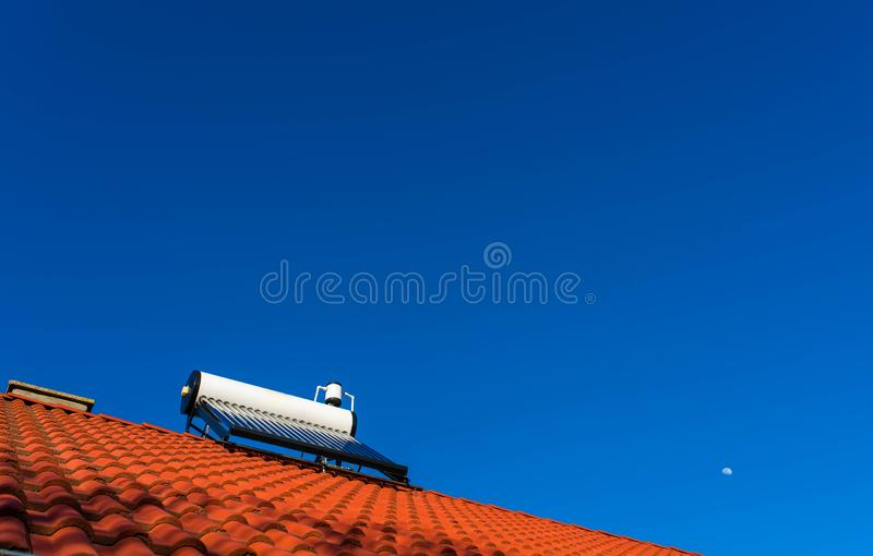 Solar water heater boiler on rooftop, visible moon, perfect blue sky background. Copy space stock photography
