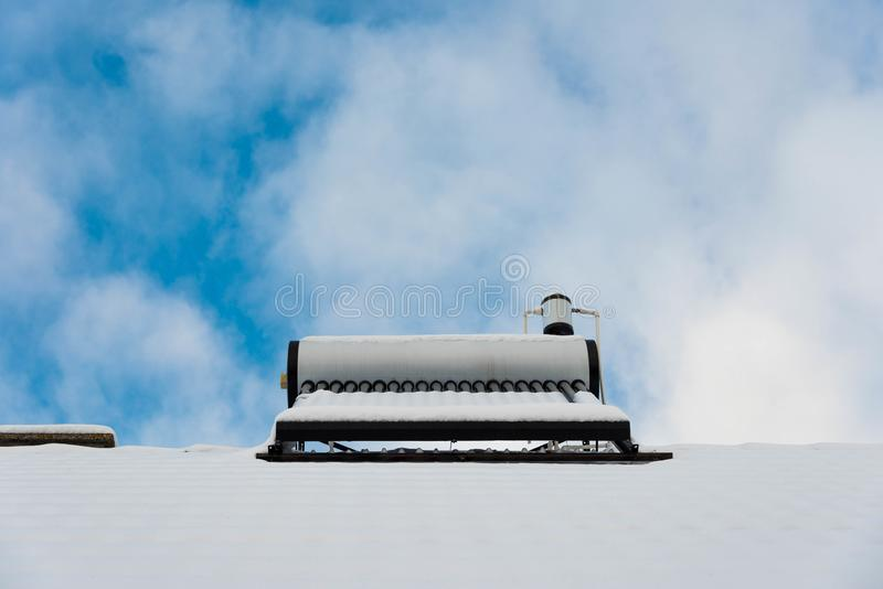 Solar water heater boiler on rooftop at winter. Blue sky with white clouds in the background royalty free stock photo