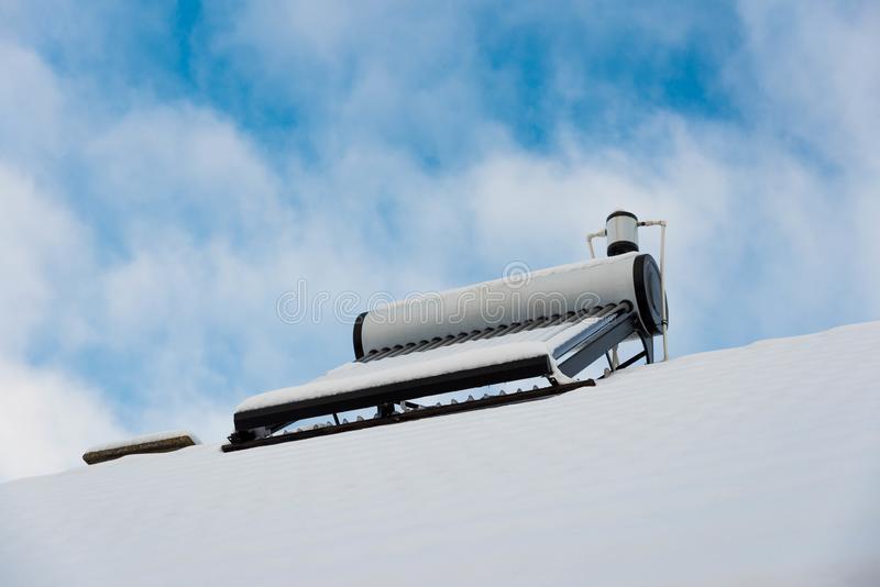 Solar water heater boiler on rooftop at winter. Blue sky with white clouds in the background stock photos
