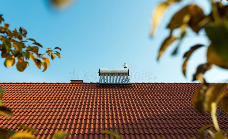 Solar water heater boiler on rooftop, yellow apple leaves. In out off focus area royalty free stock images