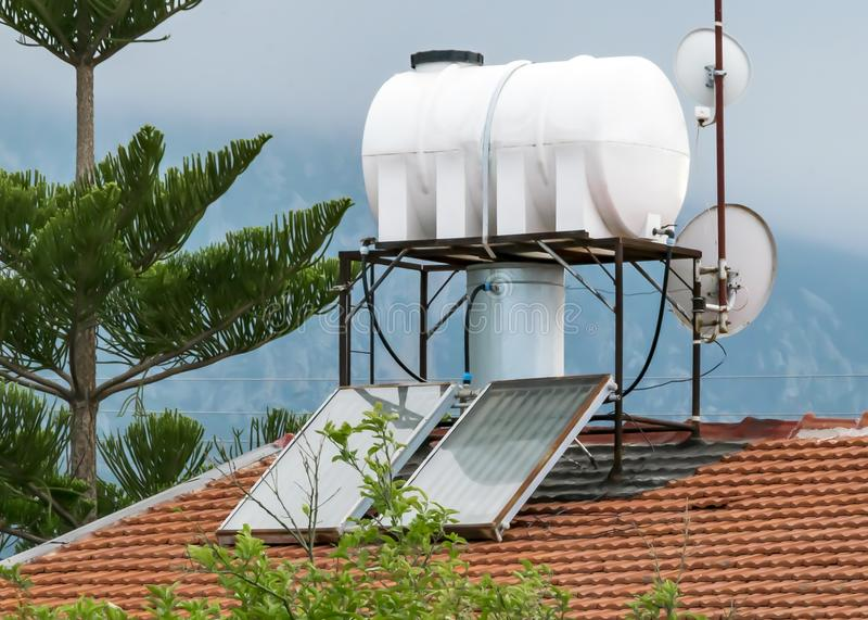 Solar water heater on country house tile roof. Alternative energy and ecology concept. stock images