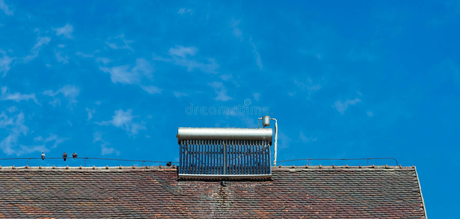 Solar water heater on old rooftop, birds, birds excrements on the water boiler royalty free stock photography