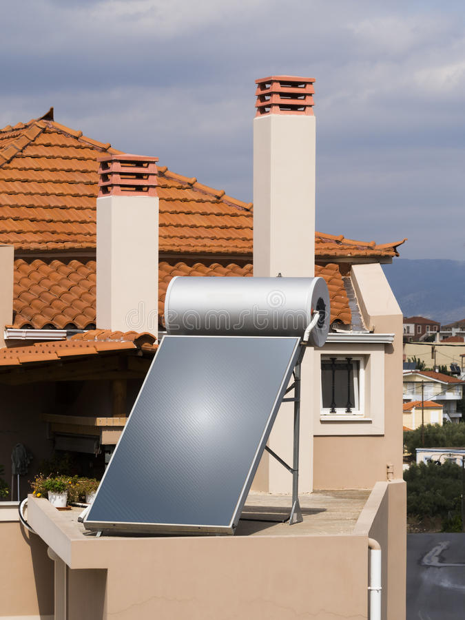 Solar water heater on roof of house. Solar water heater on roof of tile roofed house stock photos