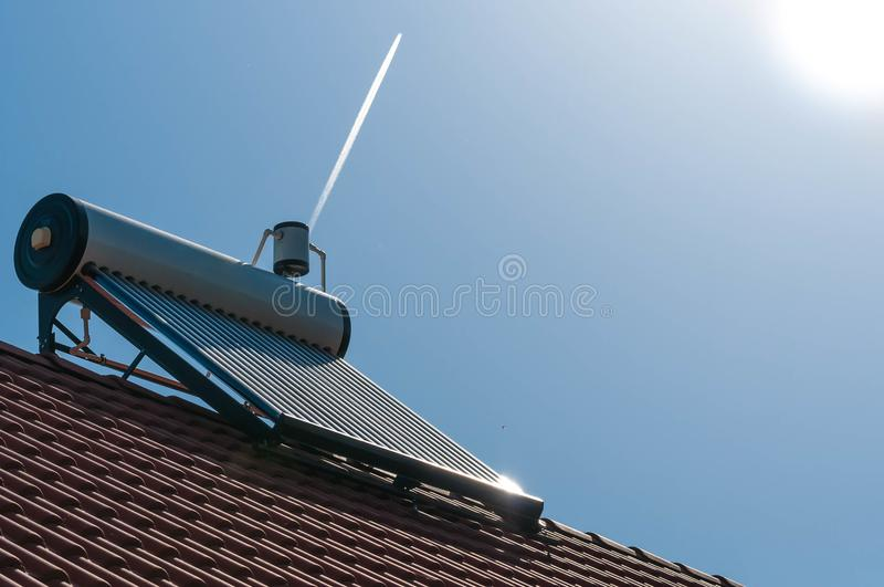 Solar water heater on roof, morning sunlight. Passing aeroplane on the blue sky royalty free stock photos