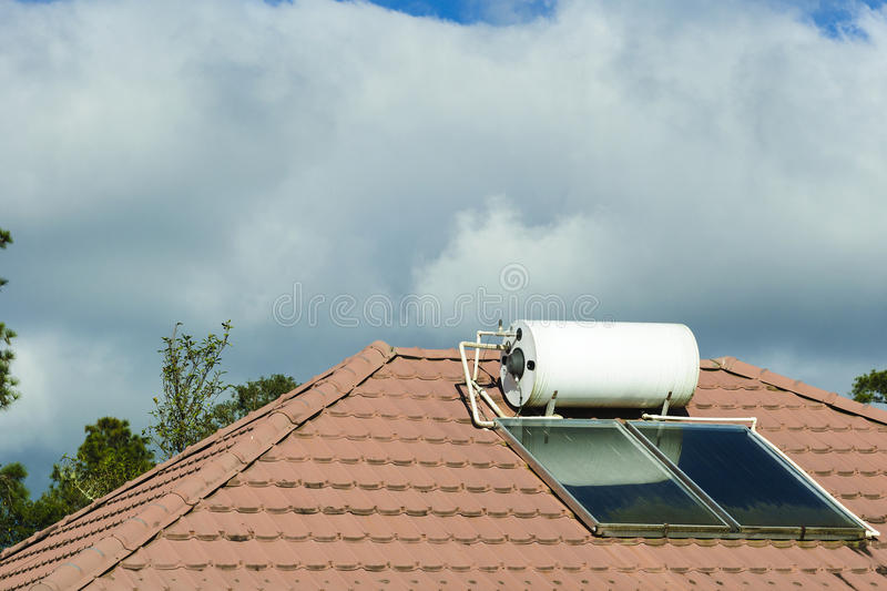 The solar water heater at the rooftop. Of the house with the cloud.The environment conservation concept stock photography